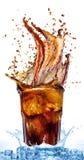 Salpique de los cubos de hielo en un vidrio de cola, aislado en el fondo blanco Fotos de archivo