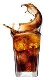 Salpique de los cubos de hielo en un vidrio de cola, aislado en el fondo blanco Imagen de archivo
