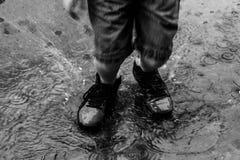 Salpique de un niño que salta en un charco de la lluvia imagenes de archivo