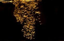 Salpique el oro amarillo del agua con las burbujas en fondo negro Foto de archivo libre de regalías