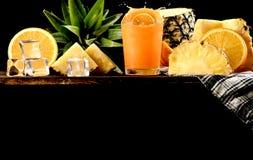 Salpique el zumo de naranja y el fondo de la piña, copia el espacio imágenes de archivo libres de regalías