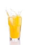Salpique en vidrio de soda anaranjada con los cubos de hielo Fotos de archivo