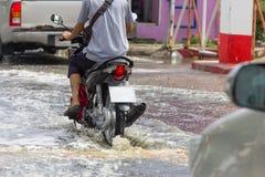 Salpique por las motocicletas como pasa a través del agua de inundación imagenes de archivo