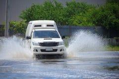 Salpique por un coche como pasa a través de la inundación fotografía de archivo