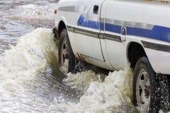 Salpique por un coche como pasa a través del agua de inundación foto de archivo libre de regalías