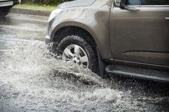 Salpique por un coche como pasa a través del agua de inundación Imagen de archivo libre de regalías