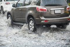 Salpique por un coche como pasa a través del agua de inundación Imagen de archivo