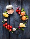 Salsa al pomodoro con l'ingrediente dei tonnidi con l'erba, le spezie ed il limone su fondo di legno blu Fotografia Stock Libera da Diritti
