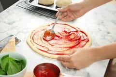 Salsa al pomodoro di diffusione della donna su pizza sulla tavola Immagini Stock Libere da Diritti