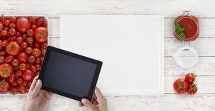 Salsa al pomodoro, mani con la compressa digitale qui sopra sulla b tagliente bianca fotografia stock libera da diritti