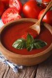 Salsa al pomodoro rossa con basilico in un primo piano di legno della ciotola verticale fotografia stock