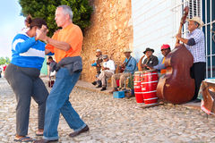 Salsa band in Trinidad. Couple dance on street while local band performing salsa music and entertain tourists in Trinidad, Cuba stock photography