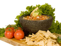 Salsa and chips. Homemade salsa in traditional Mexican molcajete mortar, fresh tomatoes and chips on white background stock image