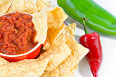Salsa and chips with peppers. Horizontal view of red bowl of hot salsa surrounded by salty tortilla chips with green anaheim and red jalapeno peppers Royalty Free Stock Image