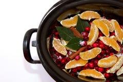 Salsa de arándano con las naranjas, el canela y la hoja de laurel que hierve a fuego lento adentro Foto de archivo