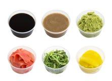 Salsa de soja, wasabi, jengibre conservado en vinagre, chuka de los rábanos y tahini en el pequeño cuenco aislado en el fondo bla Imagenes de archivo