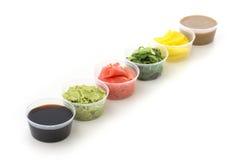 Salsa de soja, wasabi, jengibre conservado en vinagre, chuka de los rábanos y tahini en el pequeño cuenco aislado en el fondo bla Foto de archivo
