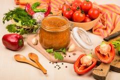 Salsa de tomate, adzhika y verduras de la salsa de tomate en una tabla beige preservación casera Fotos de archivo libres de regalías