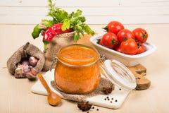 Salsa de tomate, adzhika y verduras de la salsa de tomate en una tabla beige preservación casera Fotografía de archivo libre de regalías