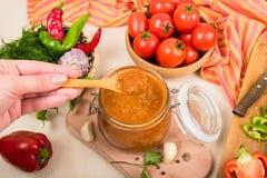 Salsa de tomate, adzhika y verduras de la salsa de tomate en una tabla beige preservación casera Foto de archivo