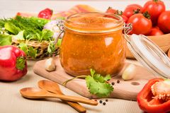Salsa de tomate, adzhika y verduras de la salsa de tomate en una tabla beige preservación casera Imágenes de archivo libres de regalías