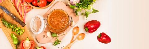 Salsa de tomate, adzhika y verduras de la salsa de tomate en una tabla beige preservación casera Imagenes de archivo