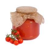 Salsa de tomate en un tarro de cristal y tomates frescos Imagen de archivo