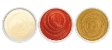 Salsa de tomate, mayonesa y mostaza aisladas en la opinión superior del fondo blanco fotos de archivo