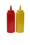Salsa de tomate plástica roja y botella plástica de la mostaza amarilla en el fondo blanco fotos de archivo libres de regalías