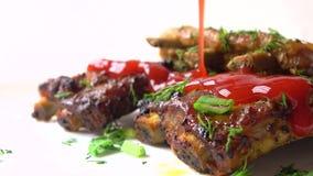 Salsa de tomate roja de colada sobre la carne recientemente cocinada Cocinar chuletas de cerdo vídeo del primer 4K almacen de video