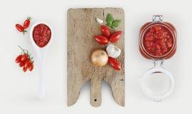 Salsa de tomates con la tabla de cortar de madera, cebolla, albahaca, ajo Imágenes de archivo libres de regalías