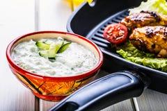 Salsa de Tzatziki Preparación de Tzatziki Tzatziki que se viste con las piernas de pollo y verduras frescas asadas a la parrilla, Fotos de archivo libres de regalías