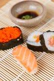 Salsa del sushi y de soja en la estera de bambú Imagen de archivo libre de regalías