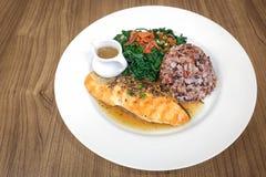 Salsa di pepe di color salmone del palo con la bacca e gli spinaci del riso con le patatine fritte fotografia stock