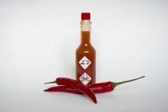 Salsa di peperoncini rossi con le etichette di avvertimento chimiche di rischio Immagini Stock