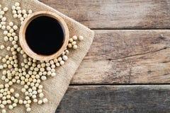 Salsa di soia della luce ultravioletta in ciotola di legno con il fagiolo della soia sul panno di sacco dell'iuta immagini stock libere da diritti