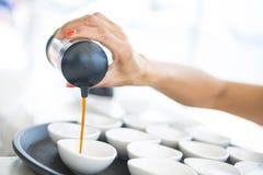 Salsa di soia di versamento nella piccola tazza immagine stock