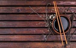 Salsa di soia e bastoncini sulla tavola di legno Immagine Stock
