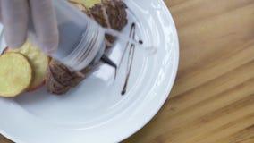 Salsa di versamento del cuoco del cuoco unico sul piatto bianco con carne arrostita ed il contorno di verdure Designazione e prog stock footage