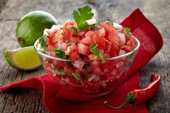 Salsa dip. Bowl of fresh salsa dip on wooden background royalty free stock image