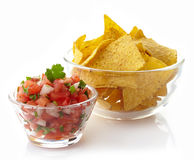 Salsa dip. Bowl of salsa dip and nachos isolated on white background stock photo