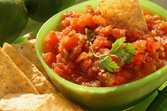 Salsa Fresca. Bowl of fresh salsa with tortilla chips and limes in background Stock Image