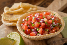 Salsa. Fresh tomato salsa with serrano pepper, red onion, green onion, lime, and cilantro in a tortilla bowl Royalty Free Stock Image