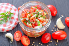 Salsa. In glass bank and fresh tomato on a table stock image