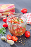 Salsa. In glass bank and fresh tomato on a table royalty free stock photo