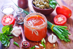 Salsa. In glass bank and on a table Royalty Free Stock Photography