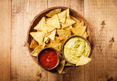 Salsa and guacamole dips with nachos chips. Fresh salsa and guacamole dips with nachos chips on wooden background royalty free stock images