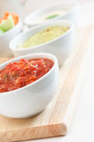 Salsa Guacamole and Hummus Dips. Close up of a bowl of tomato salsa, with guacamole, hummus dips and crudites in the background royalty free stock photos