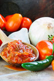 Salsa and Ingredients. Rustic wooden spoon filled with spicy fresh salsa, surrounded by freshly picked and washed ingredients spilling from an old wooden bowl royalty free stock image