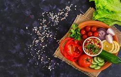 Salsa with ingredients on dark background. Top view.  royalty free stock photography